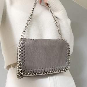 Axelväska i grå läderimitation i nyskick. Endast använd ett fåtal gånger. Nypris:450kr💕 Går att fölänga kedjan. Pris: 130kr+frakt