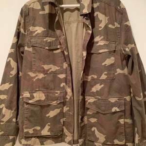 Tunn camouflage jacka från HM i storleken 36. Jackan har många fickor och stängs med knappar. Använd enstaka gånger och är i mycket bra skick.