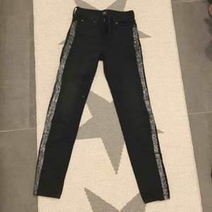 Svarta tajta jeans från Lee med glittriga silver revärer på sidorna (textilfärg, tvättas ut & in). Använda fåtal gånger, nyskick. Mellanhög midja. Ganska långa i benen.