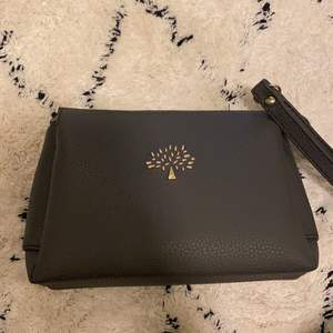 Oanvänd väska i grå färg, stora bra fickor fast liten jacka. En mindre dragkedjficka på baksidan.