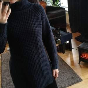 Stickad tröja i marinblå färg. Mysig och varm och går ner över rumpan (lite längre än midjelängd)