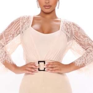 Spets body från Fashion Nova i en nude eller cream färg, storleken är S.  Bodysuiten är oanvänd och ligger kvar i sin original förpackning! Bodysuiten är väldigt snygg och passar både till vardag och fest!  Köpare får betala eventuell frakt!