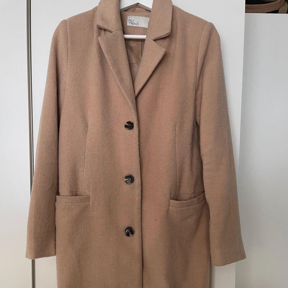 Jättetrendig beige kappa. Säljer pga bytt stil. Använd fåtal gånger. Nypris 700 kr. Högst budande!. Jackor.