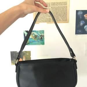 Trendig svart baguette väska i svart pläder med hulddetaljer. Väldigt rymlig, passar till allt. Mycket sparsamt använd, nästan helt ny. Pris kan diskuteras vid snabb affär :)