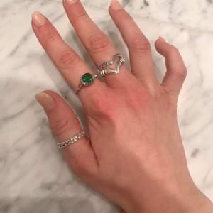 """Säljer 3 oanvända ringar. ( inte äkta silver ).                              Grön ring: 70kr                                                                                Flätad ring: 50kr                                                                           Stor ring med """"klor/tänder"""" : 50kr."""