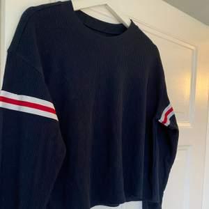 St Xs. En tröja i tunt material med två ränder på ärmarna