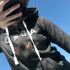 49kr för tröjan + 66kr frakt = 115kr Mörkgrå hoodie med dragkedja från Aeropostale. Fint begagnat skick. Mörkgrå med text på i vit / guldiga paljetter