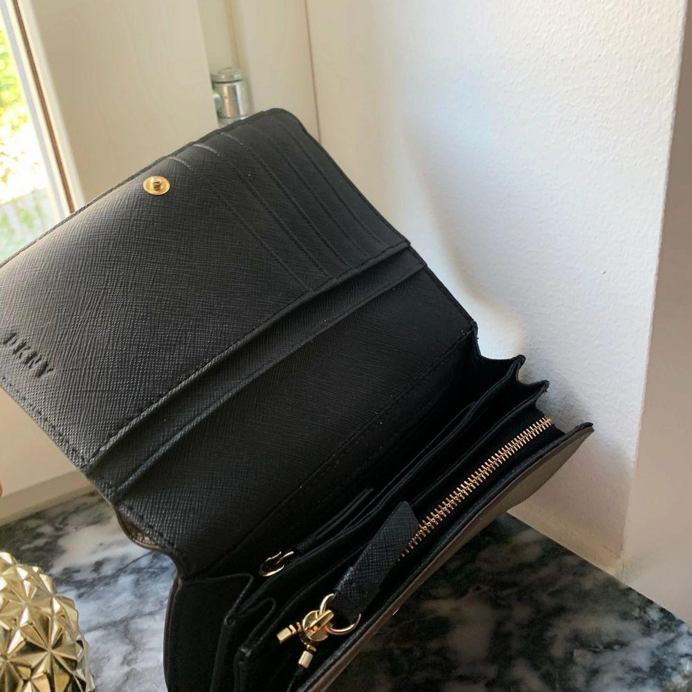 DKNY-plånbok köpt på NK. Många platser för kort samt myntfack. Färgen är gråbeige. Nypris 900kr.. Väskor.