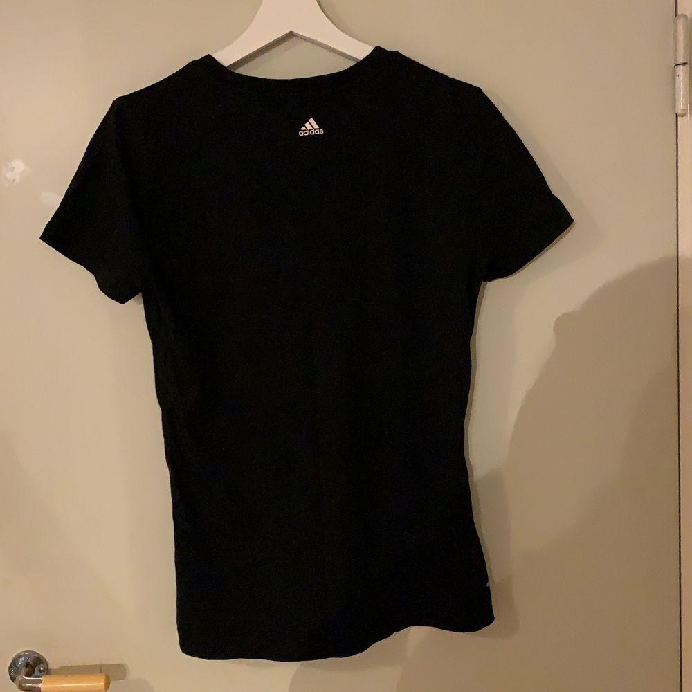 Svart Adidas t-shirts i storlek M . Med stort tryck över bröstet.. T-shirts.