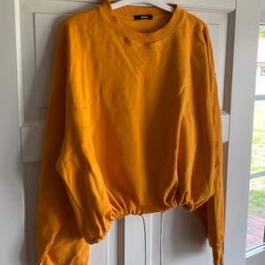 """Fin orange hoodie ( ingen luva ) från BikBok i strl S. Upplever den mer som M/L så därför jag säljer men har snören vid """"midjan"""". Använt skick men inget som är sönder eller liknande. Fortfarande fin orange färg. Köpare står för frakten."""