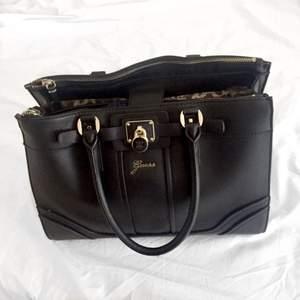 Svart handväska från GUESS, kan skicka eller mötas upp i Stockholm.