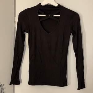 En svart ribbad tröja med ett kryss vid brösten. Tunt material i bra skick! Den är i storlek XS men passa S🤍