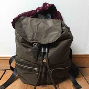Ny ryggsäck som ej använts. Dragsko upptill med knäppning på locket. Smidiga fickor fram. Scarfen medföljer och går att ta bort.