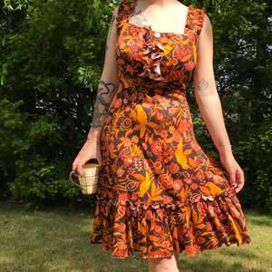Superfin vintageklänning med sköna varma färger, volanger och söta små knappar. Skriker verkligen 70-tal om den! Är i använt men fint skick, perfekt till sommarfestligheter eller till hösten med en jacka över.