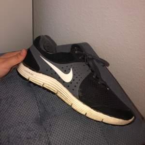 Svart och grå Nike skor, finns ett hål i tyget i en av skorna men endast i tyget och inte själva skon.