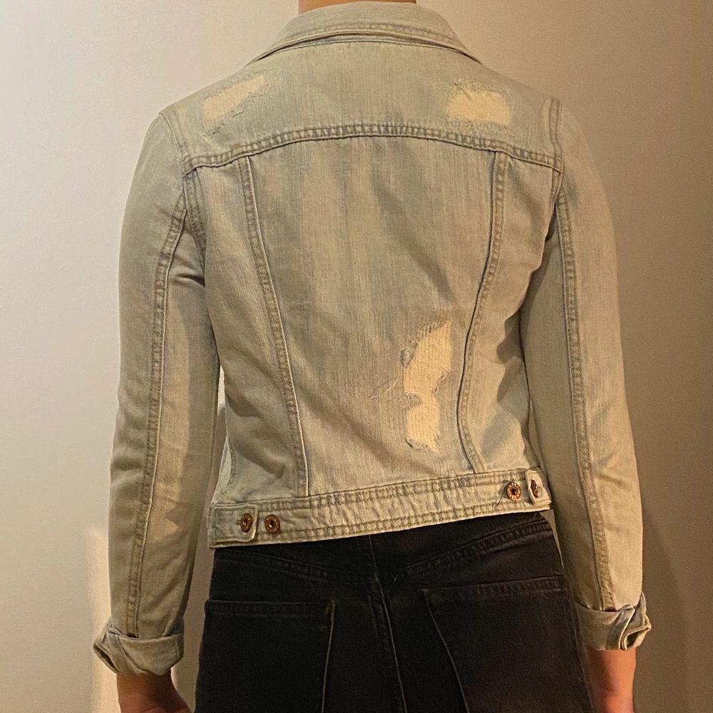 """Jeansjacka i ljusblått tyg. Med """"slitningar"""" här och där. Jättefin men liten i storleken, skulle säga xs. . Jackor."""