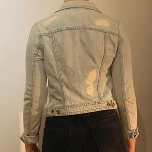 """Jeansjacka i ljusblått tyg. Med """"slitningar"""" här och där. Jättefin men liten i storleken, skulle säga xs."""