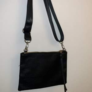En svartläder väska. Som fungerar i alla lägen. Väskan funkar att ha utan bandet också. Bandet är egentligen inte tillhörande till väskan men funkar att ha ändå.