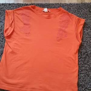 Orange t-shirt med något liknande blom/kurbits mönster på framsidan.