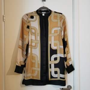 Mönstrad silkesskjorta (100% polyester) från HM x Richard Allen. Strl 36 men något tight över armarna/axlarna för mig som vanligtvis har strl 36/38. Något längre i modellen, se bild 2. Nyskick!