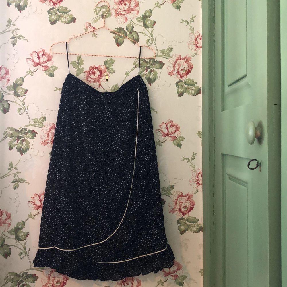 Kjolen är använd endast ett fåtal gånger och där av har den inga slitningar. Är inte genomskinlig då det ingår en mjuk, skön underkjol vilket även gör kjolen väldigt bekväm. Resor i midjan som gör att den även passar som strl 36. Materialet är polyester. . Kjolar.