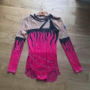 En rosa och svart rytmisk gymnastik dräkt i begagnat men fint skick. Har använts flera gånger, passar perfekt till tävlingar. Har burits på tävlingar på nationell nivå. Fint detaljerat med stenar, även Sveriges flagga på axeln. Hämtas i Kalmar