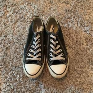 Svarta låga converse skor, sparsamt använda men lite slitna framtill på den högra skon.