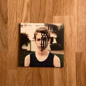 """Fall out boys album """"American beuty/american psycho"""" på cd. Limited edition upplaga med blå skiva, pappfodral och liten poster."""