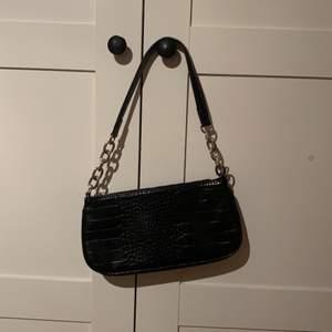 En jättefin svart baguettebag med ormsinnsmönstet inprintat i tyget på väskan. Den är helt i nyskick och bara använd några få gånger. Den har eget stort fack och sedan ett litet fack med en dragkedja på insidan. Köpt på Glitter för 249. Skriv vid intresse. HÖGSTA BUD: 70+frakt ❤️