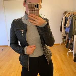 Superfin svart skinnjacka med gulddetaljer! Ej äkta skinn. Jättefint skick! Passar till alla outfits, perfekt nu till hösten!