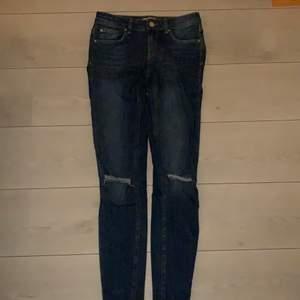 Hål vid knäna, blåa och tajta. Jeansen är ifrån Gina tricot i storlek 36.