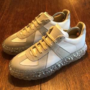 """Den klassiska modellen """"Maison Margiela Replica"""", fast med en bubbelsula. Ett par av de absolut coolaste skorna, som det franska modehuset tagit fram. Unikt utseende som drar blickar till sig. Mod. S37WS0503-White. Enbart använda två ggr av mig inomhus, dock är den högra skon något mörkare än den vänstra pga. prövad av andra kunder. Försvinner när du börjar använda dem. Nypris:6295kr"""