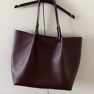 Säljer en nästan ny mörkröd shopperväska från H&M. Använd bara ~4 gånger. Väskan är jättefin. Storlek är 36 X 16 X 32 cm. Mötas / frakt kommer