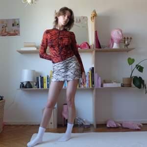 Helt sjukt perfekt tröja från DKNY. Rödbrun batikmönstrad och veckad i tyget vid dragkedjan vilket kör passningen så fin! 100% nylon. Perfekt transparens! Kan mötas upp vid stigbergstorget/gbg eller så tillkommer 22kr frakt!