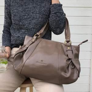 en trendig och stilren mellan-stor handväska i äkta läder från det japanska märket Hiroshima (hiroshima.hk). färgen är ljusbrun/grå med mässingsfärgade detaljer. knappt använd så mycket gott skick!! nypris ca $200 USD /2000kr.
