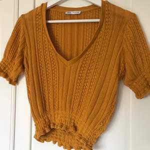 En jättefin stickad topp i färgen senapsgul. Från Zara i storlek S. Ganska urringad så det är snyggt med en tröja under men funkar utan också. Säljer pga för liten. Bra skick. 65kr + frakt.