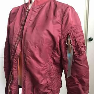 En mörkröd bomberjacka från Alpha Industries. Pyttesmå fläckar på insidan (inget man ser) och en liten slitning vid ena fickan. Men annars bra begagnat skick.