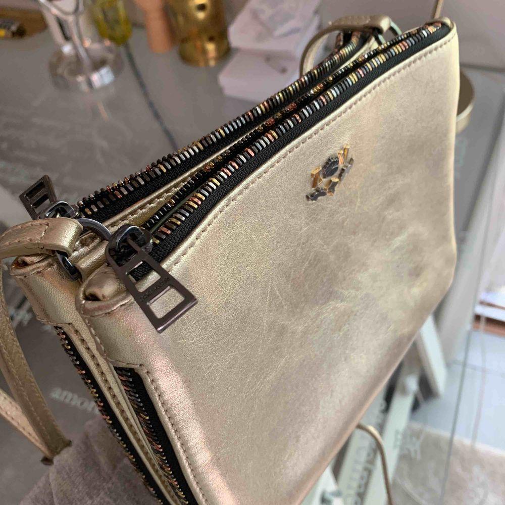 En liten väska från Zadig et Voltaire! Den har två praktiska fack med dragkedja och reglerbart axelband. Den har guldiga, silvriga och bronsaktiga detaljer under och på. Finns ej i butik. Buda från 600. Väskor.