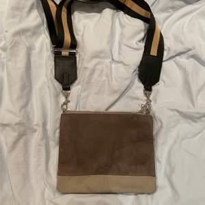 En grå väska från HM. Kommer med två band till! Ett som tillhör väskan och ett som jag köpt på Lindex! Väskan är ej använd så den är i bra skick💗60kr