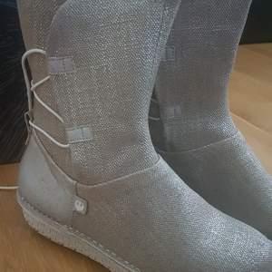 Inspirerad av Reys ikoniska mid-calf boot, som hon har på sig i Star Wars ™ episode IX: The Rise Of Skywalker. En vegansk version i naturligt linne med justerbart snörningssystem. Skonsamt använda, lådan medföljer. Org pris 1700:-