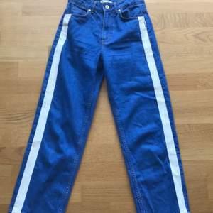 Klarblå vida jeans från zara med vit rand på sidan och hög midja. På ena benet är den vita randen sliten (se bild 3) men det syns inte jättetydligt på. Frakt tillkommer. Hör av dig vid frågor 🥰