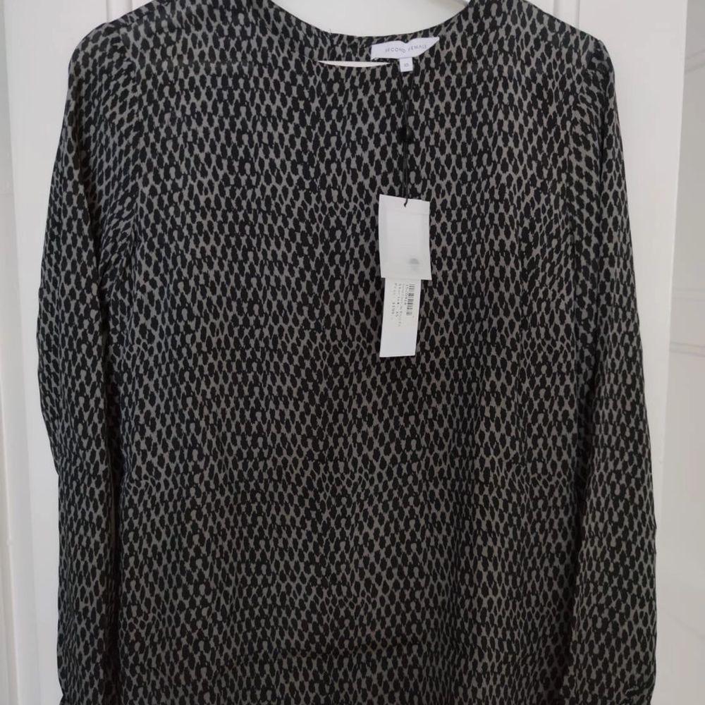Second female blus med mönster, svart-grå, strl XS, HELT NY OANVÄND. • frakt ingår  • Jag ansvarar ej för postens eventuella slarv. . Blusar.