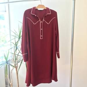 """Vinröd midi klänning från monki med fina """"western"""" detaljer vid kragen och ärmarna. Lite klockad passform och superfint fall. Hämtas i Linköping eller skickas mot frakt."""