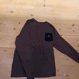 """Ascool långärmad mörkgrå adidas tröja med svart ficka och mellanblå adidaslogga på. 🖤 Mycket bra skick. Storlek XS men på mig som är en XS/S tycker jag att den sitter oversized och snyggt. Men är ganska smal längst ner i ärmarna. 100% cotton (bomull). Materialet känns som vanligt t-shirtmaterial, stretchigt, mjukt, och ganska tunt. DM vid intresse/frågor. I Dm kan jag även skicka fler bilder.❣️ (Det kan du göra här under för det står """"kontakta"""") Avhämtning på Södermalm eller frakt till självkostnadspris.:)"""