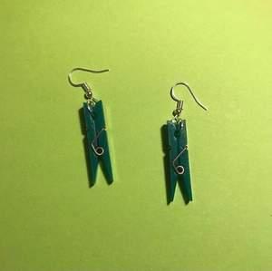 Ljusgrön klädnypa på ett guldiga örhängen. Mörkgröna klädnypor på ett par silvriga örhängen. Väldigt gulliga :) ett par örhängen kostar 30kr