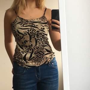 skitnajs leopard linne i storlek S, men passar mig som ofta har storlek M. Linnet består tunt svart tug underst och ett andra lager med leopard mönster. Banden är justerbara