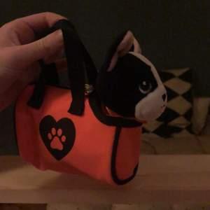 En gosedjurs hund med väska. Väskan har dragkedja och handtag. Tyvär klippte jag bort lappen när jag var liten. Priset går att diskutera!