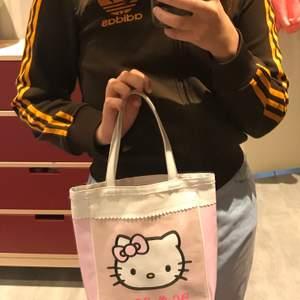 Glittrig hello Kitty väska i plast. Korta handtag.