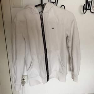 Vit hoodie med dragkedja från tommy hilfiger, sparsamt använd och i nyskick, storlek xs men passar också S