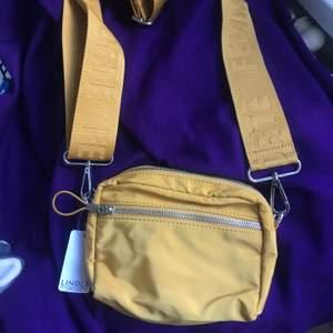 En gul liten axelremsväska från Lindex💕 Helt oanvänd, prislappen är kvar! Bandet är justerbart
